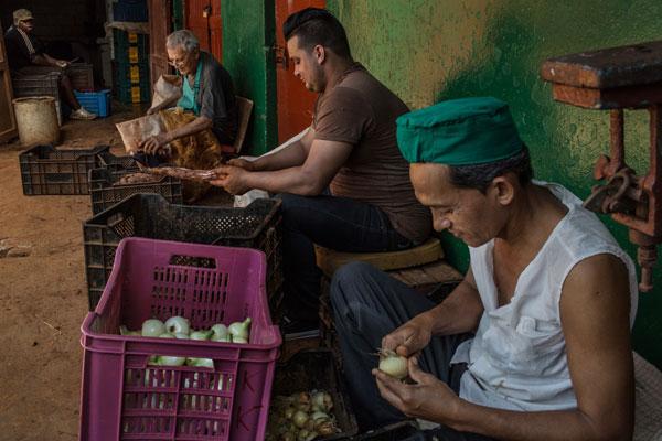 Trabajadores limpian algunos  vegetales en un mercado de frutas ubicado en la Ha