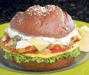 Sandwich de pollo y vegetales en pan de centeno con aderezo Cesar.
