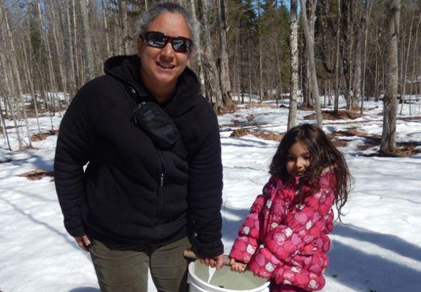 Julia Patricia y Jumi recolectan savia de maple durante un paseo educativo.