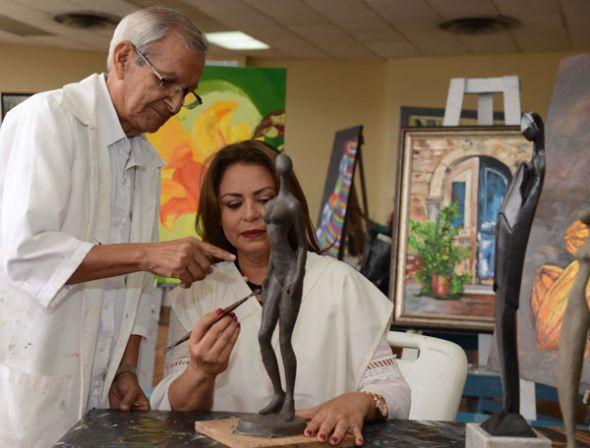 Abdón Calderón enseña escultura a Stela Riera.