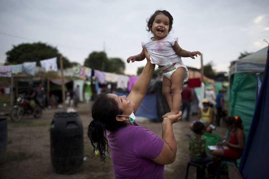 Patricia Zambrano juega con su nieta en una carpa improvisada por familias.